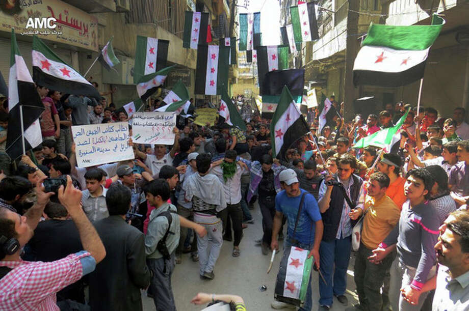 """This citizen journalism image provided by Aleppo Media Center AMC which has been authenticated based on its contents and other AP reporting, shows anti Syrian regime protesters holding banners and waving the Syrian revolutionary flags during a demonstration, in Aleppo, Syria, Friday, April 26, 2013. Araboc on banners read: """"we call upon the Free Syrian Army brigades and the Mujahedeen to stop the military convoy in the city of al-Safira,"""" left, and """"all what Kerry has is the laughing cow cheese .""""(AP Photo/Aleppo Media Center AMC) / Aleppo Media Center AMC"""