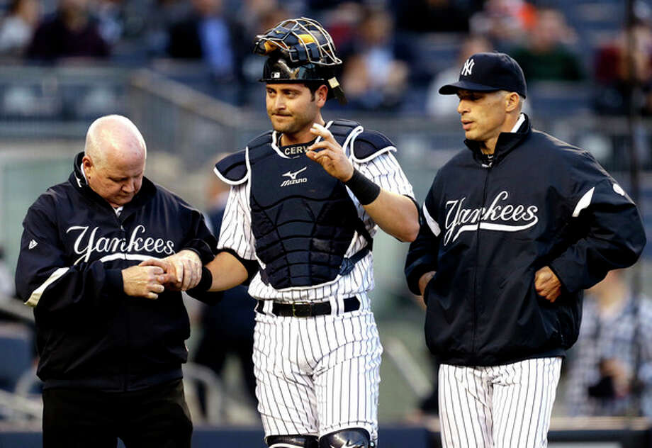New York Yankees trainer Steve Donohue, left, checks on catcher Francisco Cervelli, center, as manager Joe Girardi looks on during the first inning of a baseball game against the Toronto Blue Jays at Yankee Stadium in New York, Friday, April 26, 2013. Cervelli left the game. (AP Photo/Julio Cortez) / AP