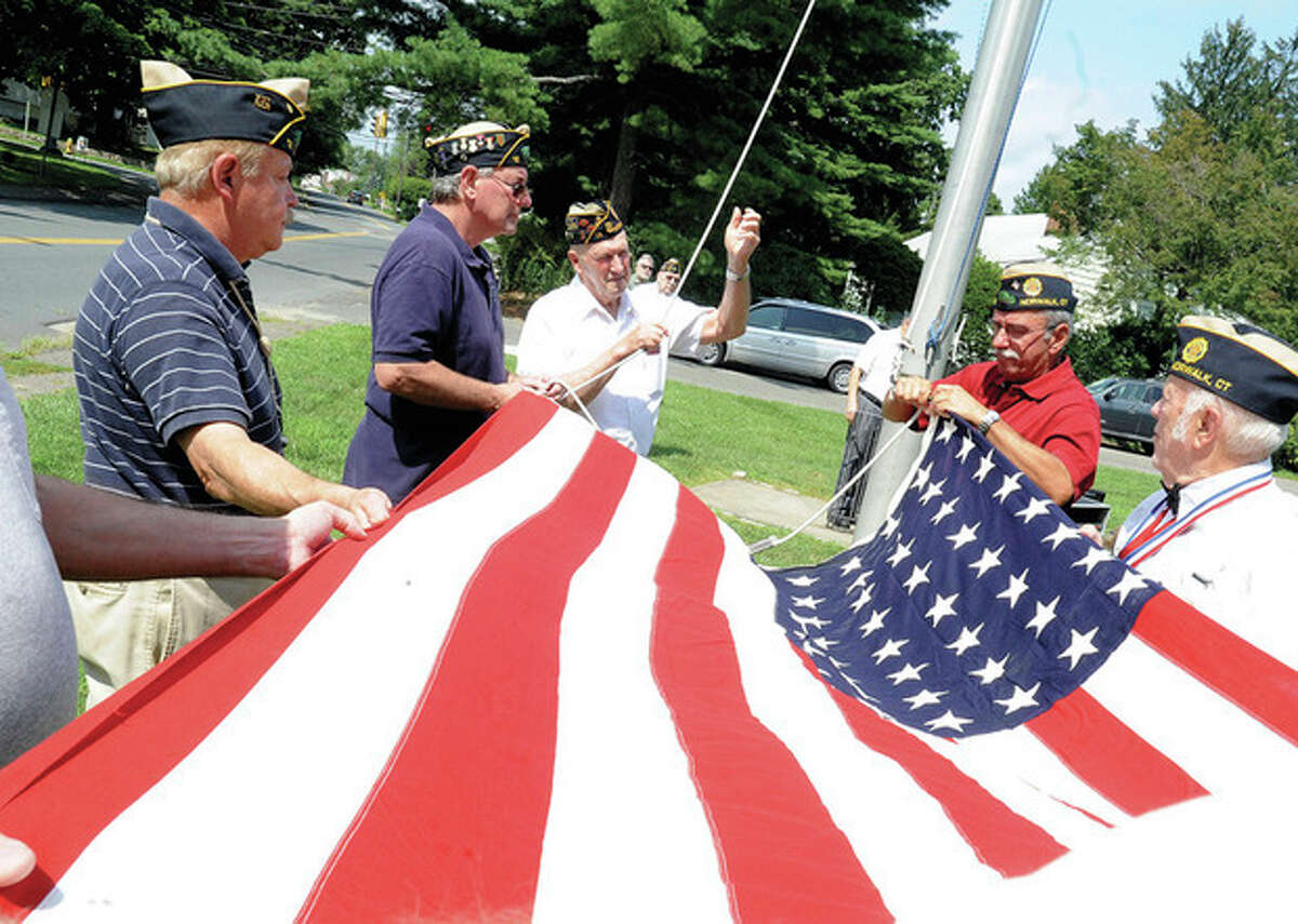 Hour photo / Matthew Vinci Members of the American Legion Post 12 in Norwalk raise a 48-star flag Sunday for veteran of the month Philip Roger Marzolf, who served in the Korean War as a Navy corpsman attached to the Marines.
