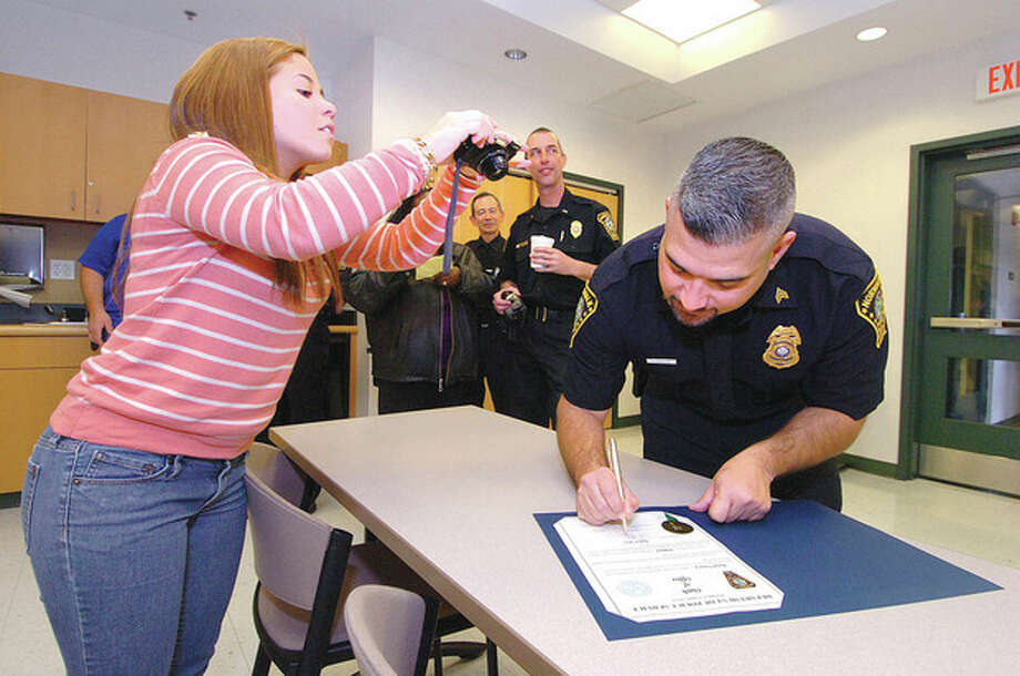 Hour Photo/Alex von KleydorffAt a promotion ceremony at Police Headquarters Detective Rafael Fonseca is promoted to Sergeant and signs the Oath of Office as his daughter Maelanie takes a photo to capture the moment. / 2013 The Hour Newspapers
