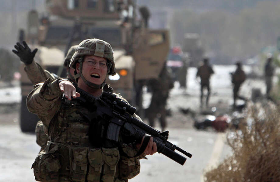 A US soldier reacts while seen at the site of a suicide car bomber in Kabul, Afghanistan, Saturday, Oct. 29, 2011. A suicide car bomber struck a NATO convoy on the outskirts of Kabul on Saturday, causing casualties among the NATO service members and Afghan civilians, the U.S.-led coalition said. Afghan officials said three civilians and one policeman were killed. (AP Photo/Muhammed Muheisen) / AP