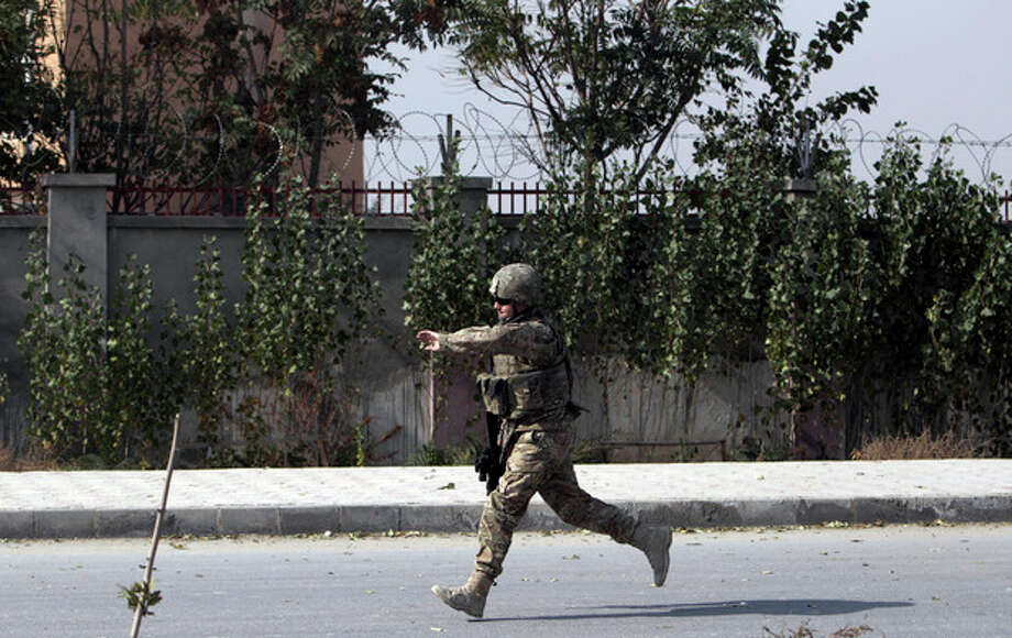 A US soldier runs to the site of a suicide car bomber in Kabul, Afghanistan, Saturday, Oct. 29, 2011. A suicide car bomber struck a NATO convoy on the outskirts of Kabul on Saturday, causing casualties among the NATO service members and Afghan civilians, the U.S.-led coalition said. Afghan officials said three civilians and one policeman were killed. (AP Photo/Muhammed Muheisen) / AP