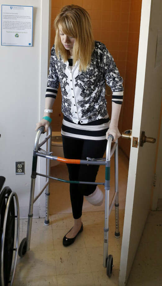 Adrianne Haslet, a a professional ballroom dancer injured by one of the bombs that exploded near the Boston Marathon finish line, uses a walker to return to her bed at Spaulding Rehabilitation Hospital in Boston, Wednesday, April 24, 2013. Haslet, who lost her left foot and part of her lower leg, vows that she will dance again. (AP Photo/Bizuayehu Tesfaye)