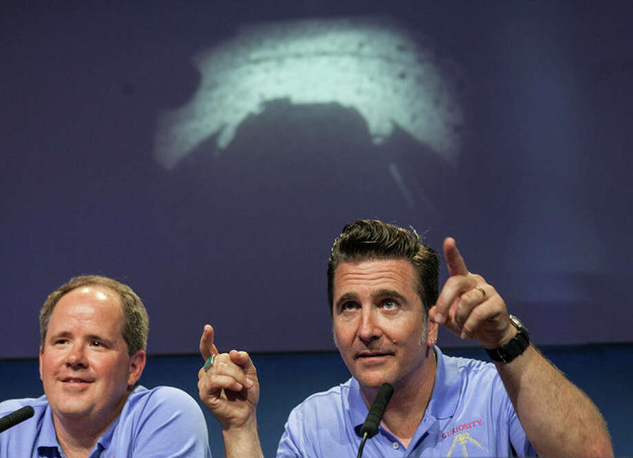Mars Science Laboratory Curiosity Richard Cook, MSL deputy project manager, left, and Adam Steltzner, MSL entry, descent and landing (EDL) lead, right, point to the first image taken by NASA's Curiosity rover, which landed on Mars the evening of Aug. 5 on the surface of Mars, during a news conference at NASA's Jet Propulsion Laboratory in Pasadena, Calif., Sunday, August 5, 2012. (AP Photo/Damian Dovarganes) / AP
