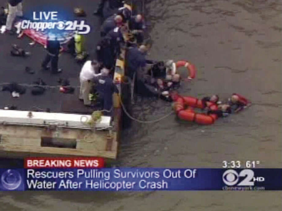 In this frame grab image taken from WCBS-TV, survivors are pulled to a pier by rescue personnel following a crash in the East River in New York, Tuesday Oct. 4, 2011. The New York Police Department says the helicopter with five people aboard crashed into the river after taking off from a nearby heliport. The pilot and three others were pulled from the water shortly by rescue crews after it went down. Authorities were still searching for one other passenger, believed to be female, but the helicopter was fully submerged. (AP Photo/WCBS-TV) MANDATORY CREDIT WCBS-TV / WCBS TV