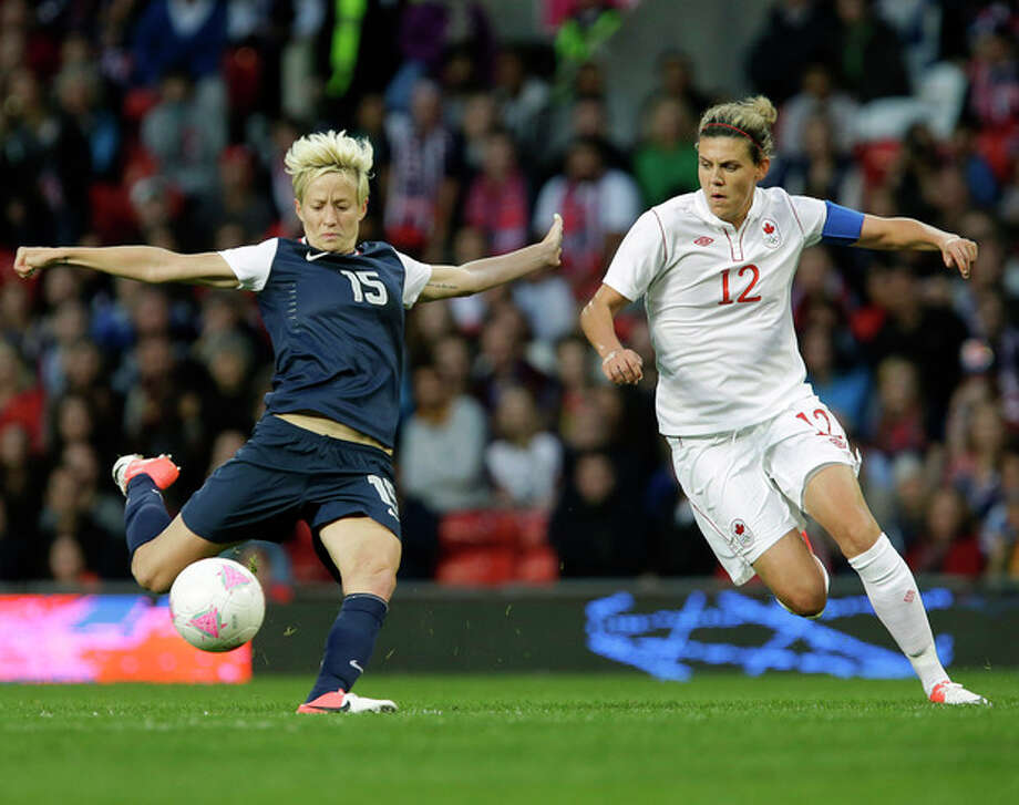 United States' Megan Rapinoe, left, prepares to kick the ball against Canada's Christine Sinclair, right, during their semifinal women's soccer match at the 2012 London Summer Olympics, in Manchester, England, Monday, Aug. 6, 2012. (AP Photo/Hussein Malla) / AP