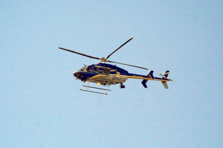 A CT State Police Helicopter flies around the Stamford Marriott Monday afternoon where President Obama made an appearance. Hour Photo / Danielle Robinson