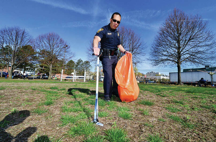 Norwalk police officer Sean Wong Won picks up trash at Ryan Park as part of a Community Clean-Up Day to spruce up South Norwalk.Hour photo / Erik Trautmann / (C)2013, The Hour Newspapers, all rights reserved