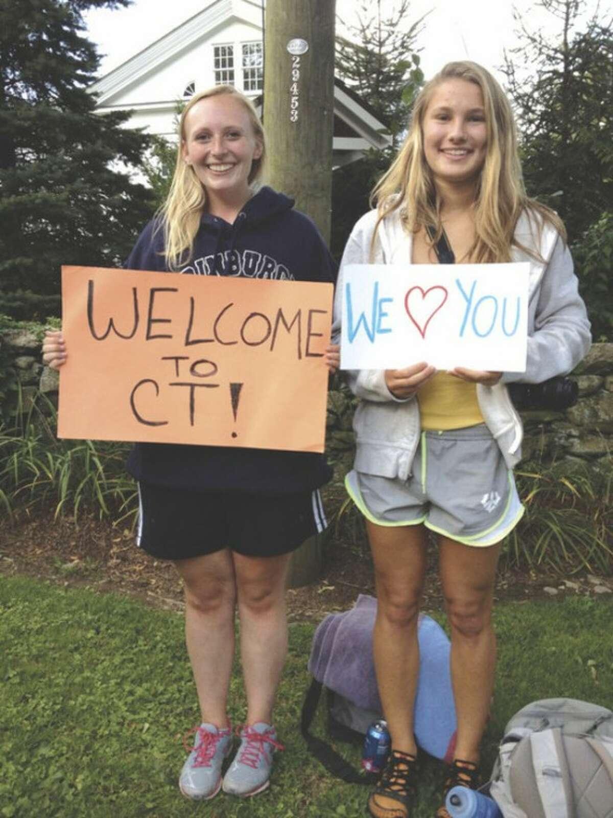 Hour photo / Robin Kaminski From left, Anna Burns and Annika Heumann, both of Fairfield, welcome President Obama to Conn.