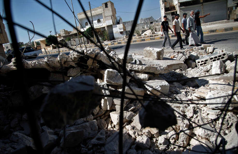 In this Sunday, Aug. 5, 2012 photograph, Syrians pass by a destroyed house in town of Atareb outskirts of Aleppo, Syria. (AP Photo) / AP