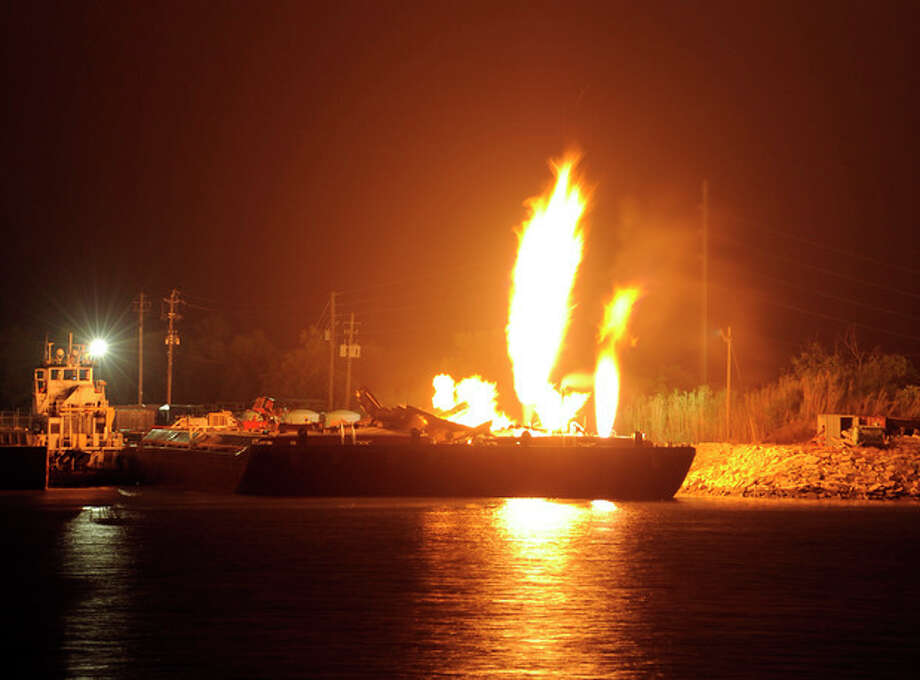 Fire burns aboard two fuel barges along the Mobile River after explosions sent three workers to the hospital Wednesday April 24, 2013. Fire officials have pulled units back from fighting the fire due to the explosions and no immediate threat to lives. (AP Photo John David Mercer) / AP