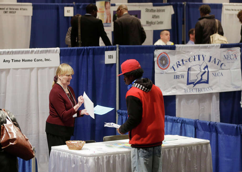 In this Thursday, April 11, 2013, photo, Kathie Maiello of Any-Time Home Care, left, talks with Jashod Chaney of Albany at the Dr. King Career Fair at the Empire State Plaza Convention Center, in Albany, N.Y. The Labor Department reports on the number of Americans who applied for unemployment benefits last week on Thursday, April 25, 2013. (AP Photo/Mike Groll) / AP