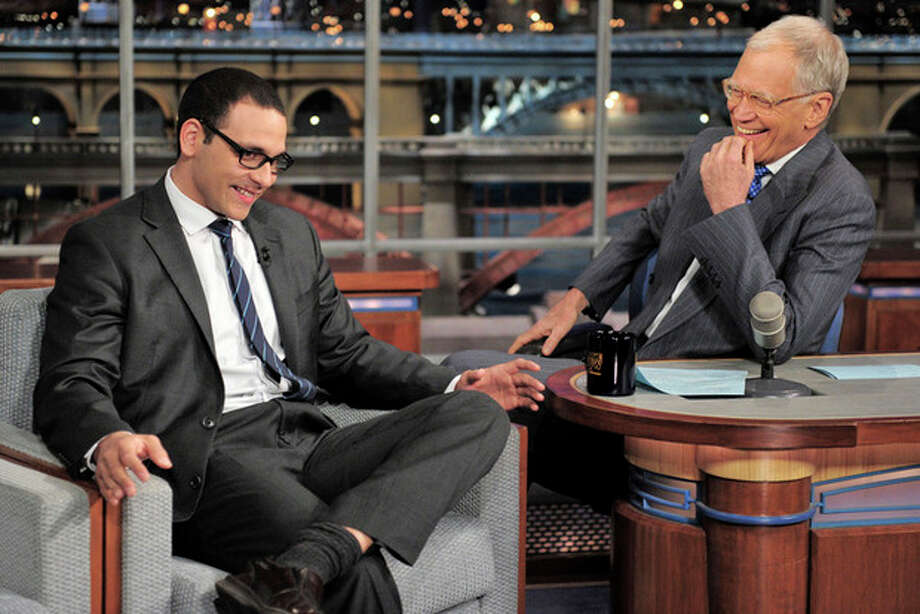"""In this photo provided by CBS, former news anchor A.J. Clemente, left, has a laugh with host David Letterman on the set of the """"Late Show with David Letterman,"""" Wednesday, April 24, 2013 in New York. Clemente explained how he got fired on his first day from his television anchor job in Bismarck, N.D. (AP Photo/CBS, John Paul Filo) / CBS"""