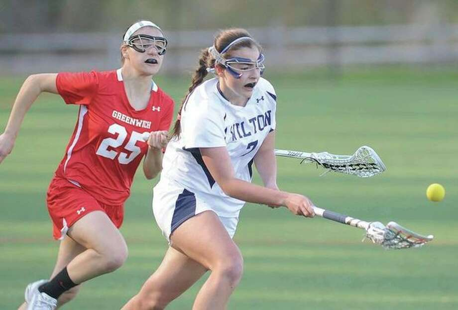 Hour photo/John NashWilton's Annie Cornbrooks, right, gathers in a ground ball before Greenwich's Danielle Ravele cam make a play on it during the second half of Thursday's FCIAC game at Lilly Field.