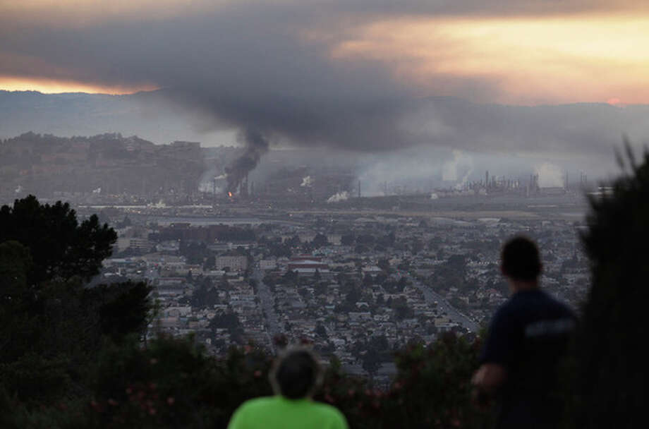 People watch smoke rise from the Chevron refinery in Richmond, Calif., from a vantage point in the El Cerrito, Calif., hills Monday, Aug. 6, 2012. Officials have told residents of two Northern California cities to shelter-in-place as a fire at a Chevron refinery in Richmond releases plumes of black smoke. (AP Photo/The Daily Republic, Brad Zweerink) MANDATORY CREDIT / The Daily Republic