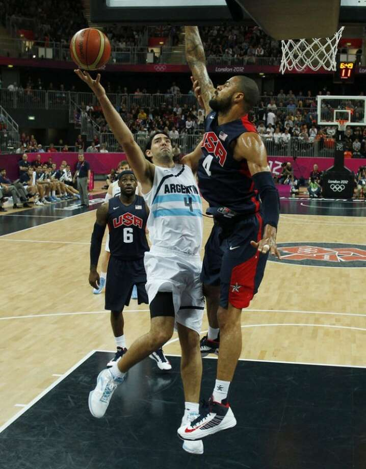 Argentina's Luis Scola, left, goes in for a lay-up as Tyson Chandler, right, of the United States guards during a men's basketball preliminary round match at the 2012 Summer Olympics, Monday, Aug. 6, 2012, in London. (AP Photo/Mike Segar, Pool)