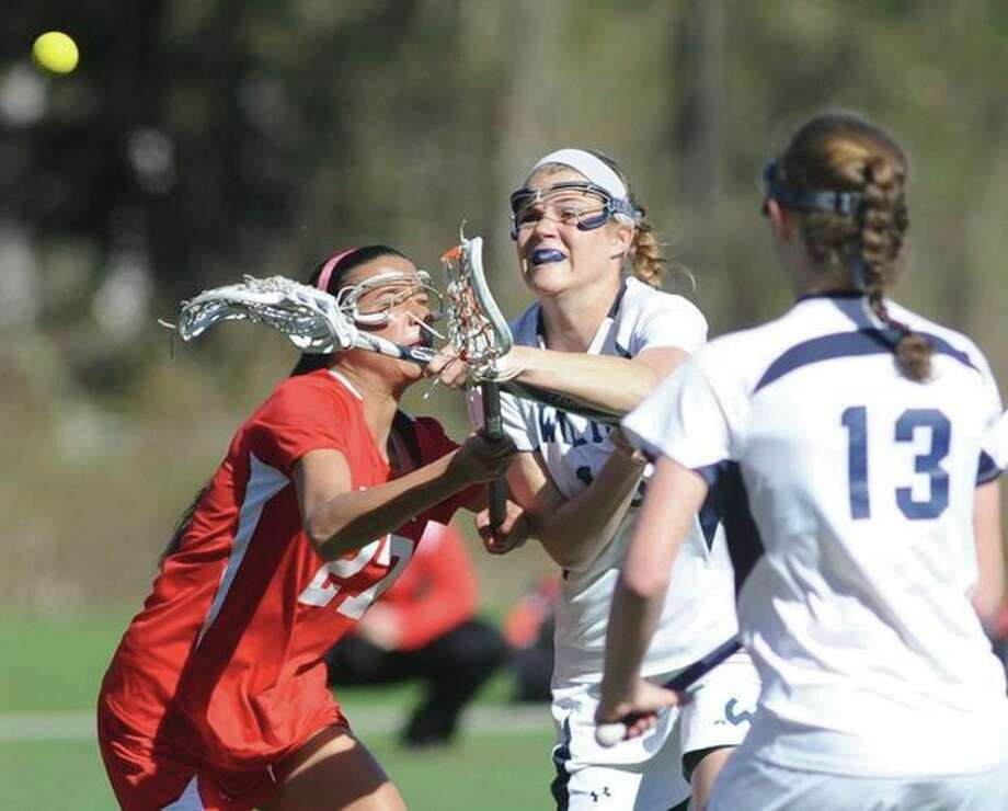 Hour photo/John NashWilton's Tegan Helms, center, fires off a shot against Greenwich defender Carolyn Patella as the Warriors Makenna Pearsall looks on during the first half of Thursday's FCIAC game at Kristine Lilly Field in Wilton. The visiting Cardinals claimed a 10-8 victory.