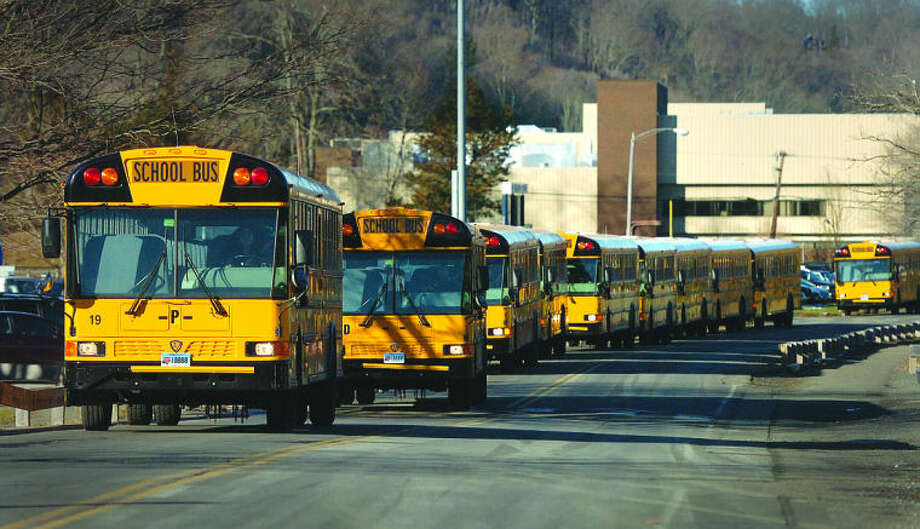 School buses travel down Kristine Lilly Way from Wilton High School in this file photo.