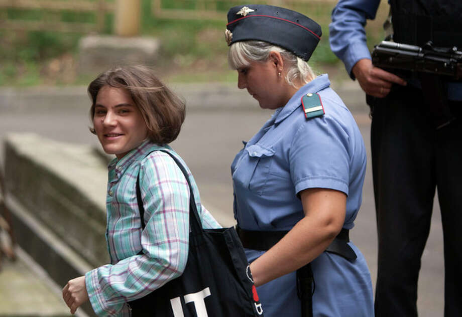 """Yekaterina Samutsevich, left, a member of feminist punk group Pussy Riot is escorted to a court room in Moscow, Russia, Tuesday, Aug. 7, 2012. Russia's President Vladimir Putin on Thursday criticized the feminist punk rockers facing trial for performing a """"punk prayer"""" against him at Moscow's main cathedral, but said that a punishment for them shouldn't be too severe. (AP Photo/Alexander Zemlianichenko) / AP"""