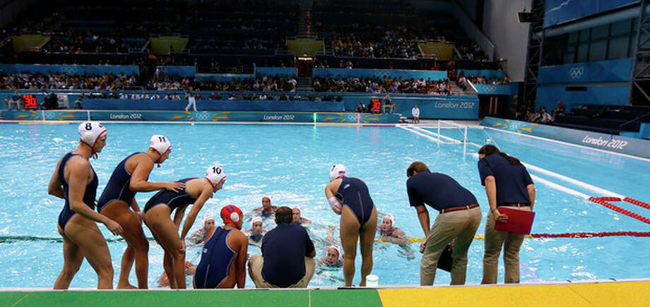 Members of the United States water polo team gather round during the final timeout in overtime during their women's semifinal water polo match against Australia at the 2012 Summer Olympics, Tuesday, Aug. 7, 2012, in London. (AP Photo/Alastair Grant) / AP
