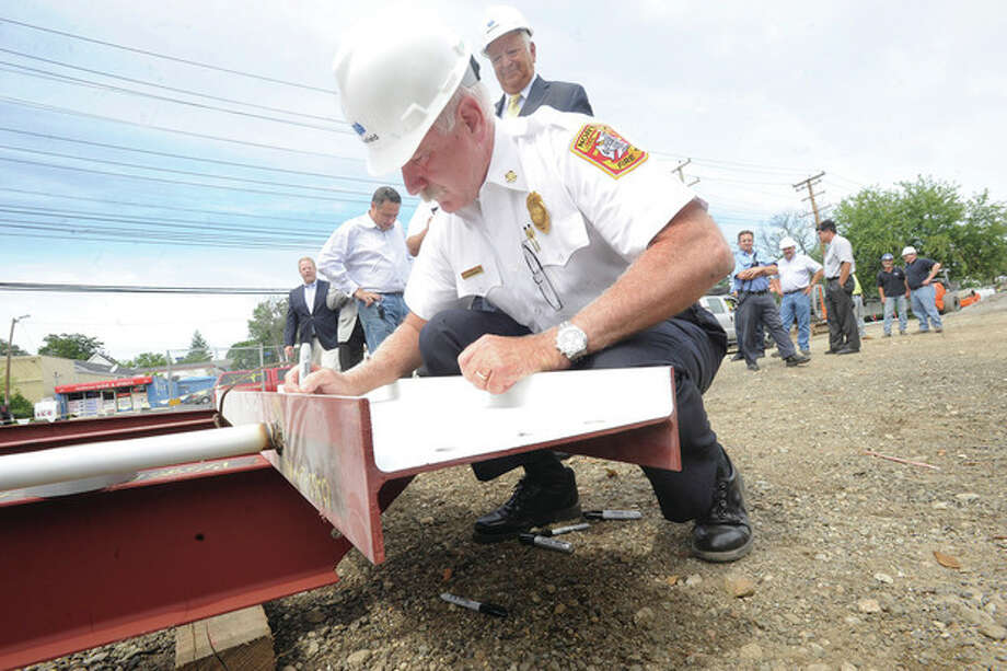 "Hour photos / Matthew VinciNorwalk Fire Chief Denis McCarthy signs the last piece of of structural steel Tuesday at the ""top out"" ceremony for the new central fire station in Norwalk."