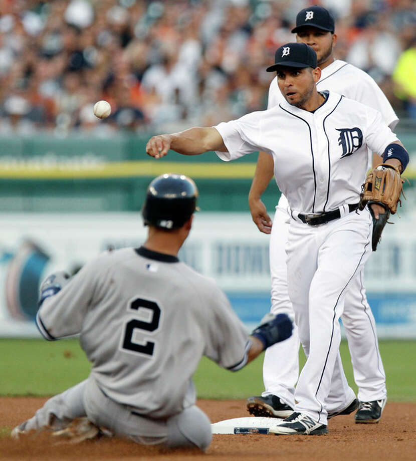 Detroit Tigers second baseman Omar Infante, with shortstop Jhonny Peralta, rear, watching, throws to first after forcing out New York Yankees' Derek Jeter (2) in the fourth inning of a baseball game Tuesday, Aug. 7, 2012, in Detroit. Robinson Cano was out at first base. (AP Photo/Duane Burleson) / FR38952 AP