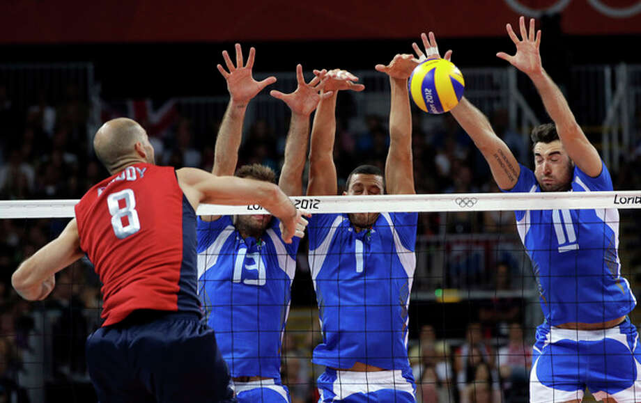 From left, United States' William Priddy spikes the ball past Italy's Dragan Travica, Luigi Mastrangelo and Cristian Savani during a men's quarterfinal volleyball match between the United States and Italy, at the 2012 Summer Olympics, Wednesday, Aug. 8, 2012, in London. (AP Photo/Andrew Medichini) / AP