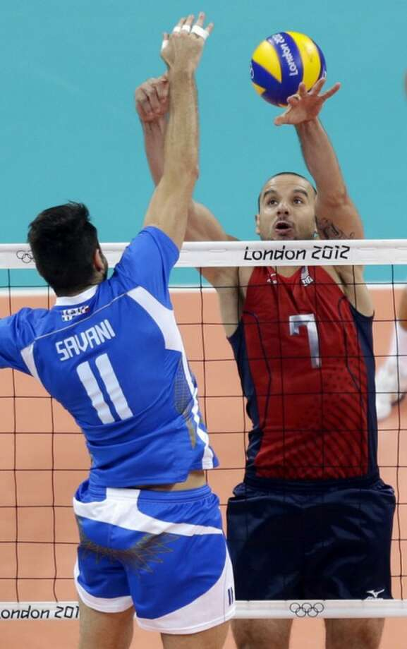 Italy's Cristian Savani (11) spikes the ball past USA's Donald Suxho (7) during a men's volleyball quarterfinal match at the 2012 Summer Olympics Wednesday, Aug. 8, 2012, in London. (AP Photo/Chris O'Meara)