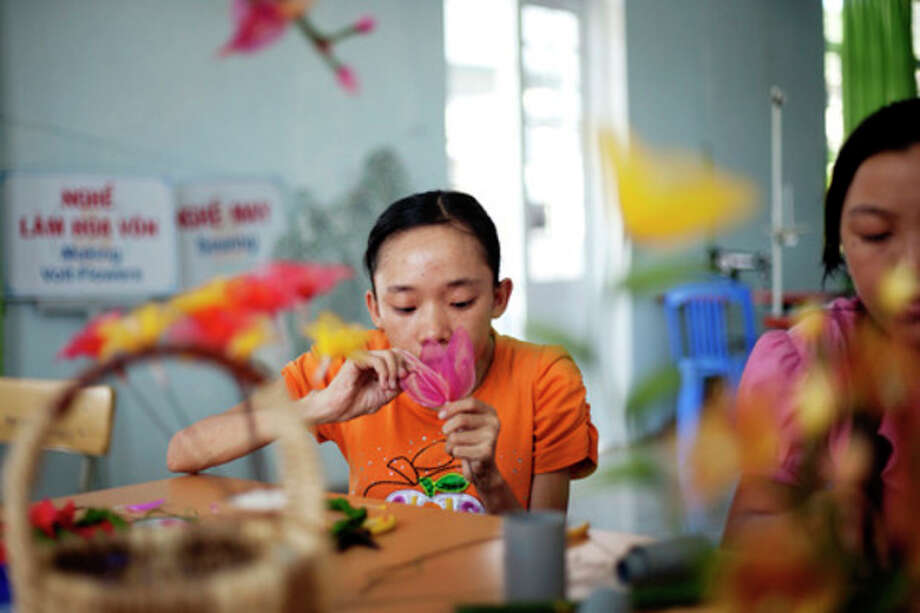 In this photo taken Aug. 7, 2012, Ho Thi Lang, 18, left, and Pham Thi Thuy Linh, 21, learn how to make artificial flowers at the supporting center for victims of Agent Orange in Danang, Vietnam. The children were born with physical and mental disabilities that the center's director said were caused by their parents' exposure to the chemical dioxin in the defoliant Agent Orange. Washington was slow to respond, but on Thursday, Aug. 9, 2012 the U.S. for the first time will begin cleaning up leftover dioxin that was stored at the former military base, now part of Danang's airport. (AP Photo/Maika Elan) / AP