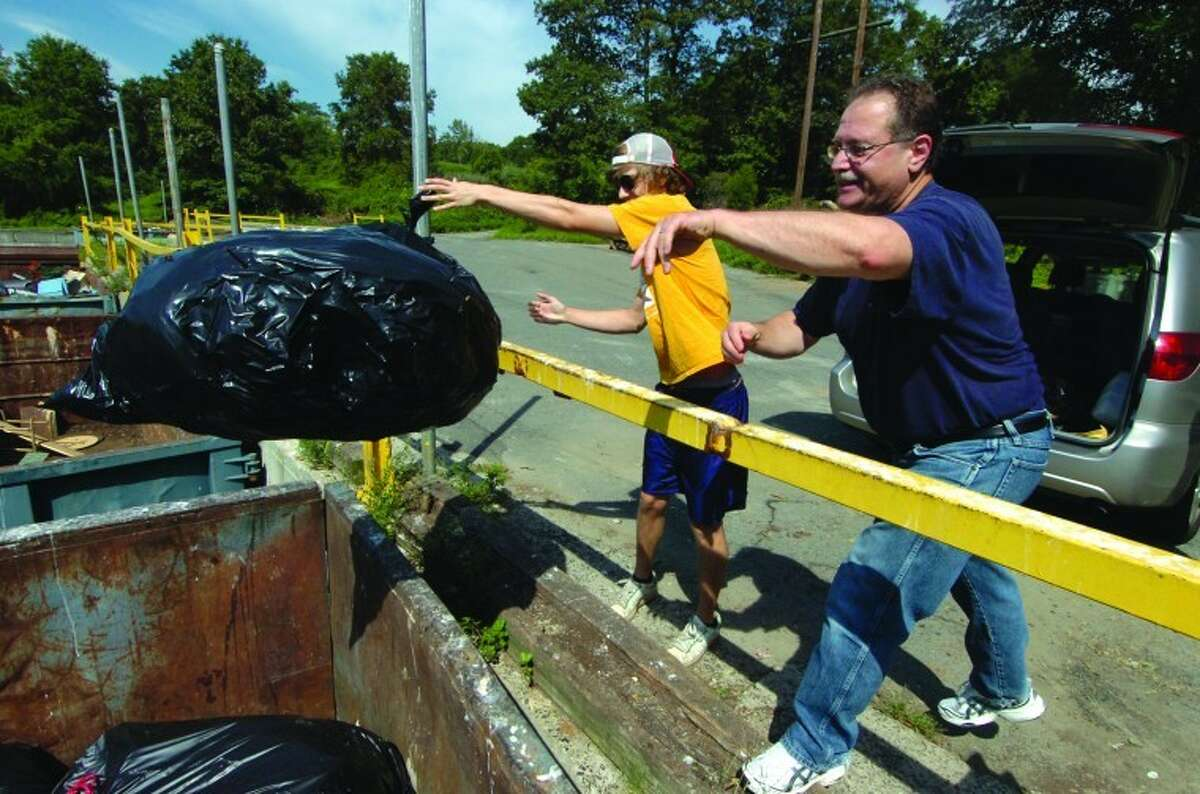 File Photo/ Alex von Kleydorff. Wilton's Joe DeGirolamo and son Chris chuck the spoiled contents of their refridgerator and freezer into a container at the Wilton Transfer Station. The family lost power last summer during Tropical Storm Irene.