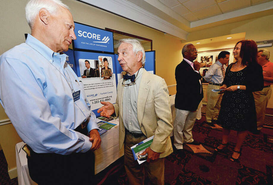 SCORE counselor Dave Conrod chats with Scott Kimmich during the Small Business Expo State hosted by Senator Bob Duff (D-Norwalk) and the Greater Norwalk and Darien Chambers of Commerce Wednesday at the Hilton Garden Inn.Hour photo / Erik Trautmann / (C)2012, The Hour Newspapers, all rights reserved
