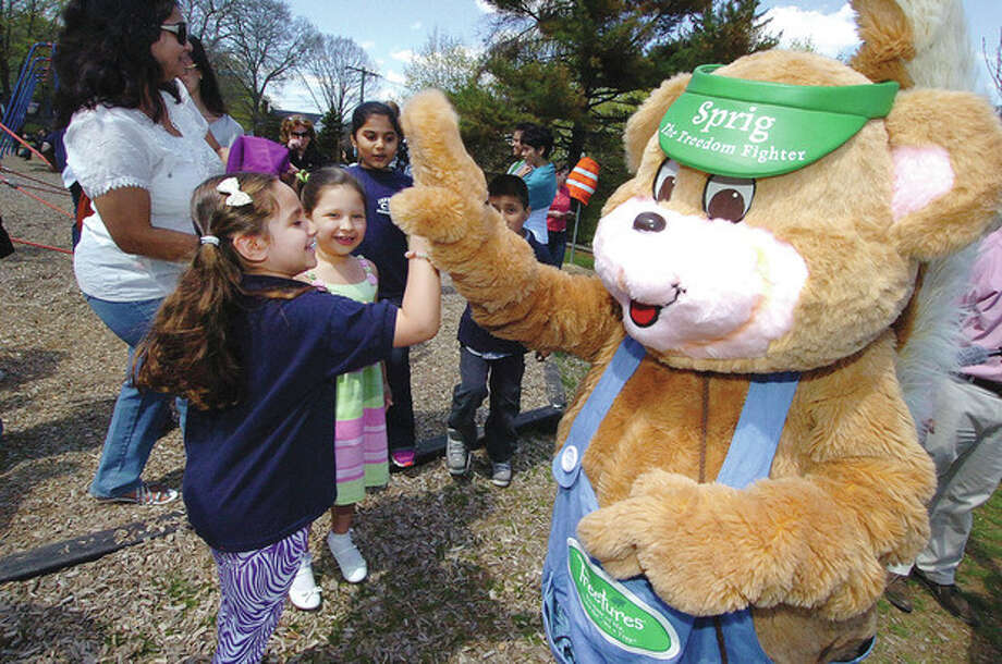 Hour photo / Alex von Kleydorff'Sprig' gets a high five from Jefferson Science Magnet School first-grader Anabella Silva at the Arbor Day ceremony in Norwalk on Friday. / 2013 The Hour Newspapers