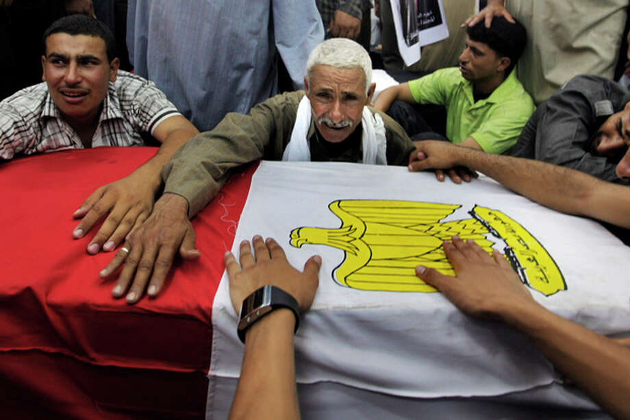FILE - In this Tuesday Aug. 7, 2012 file photograph, relatives of an Egyptian soldier mourn during the funeral of one of 16 soldiers killed in an attack over the weekend by suspected militants in Sinai in Cairo, Egypt. After decades of neglect and with the collapse of government authority the past 18 months, Egypt's Sinai Peninsula has become fertile ground for Islamic extremists. Militant groups have taken root, carrying out attacks against neighboring Israel and now turning their guns against Egypt's military as they vow to set up an Islamic state. (AP Photo/Amr Nabil, File) / AP