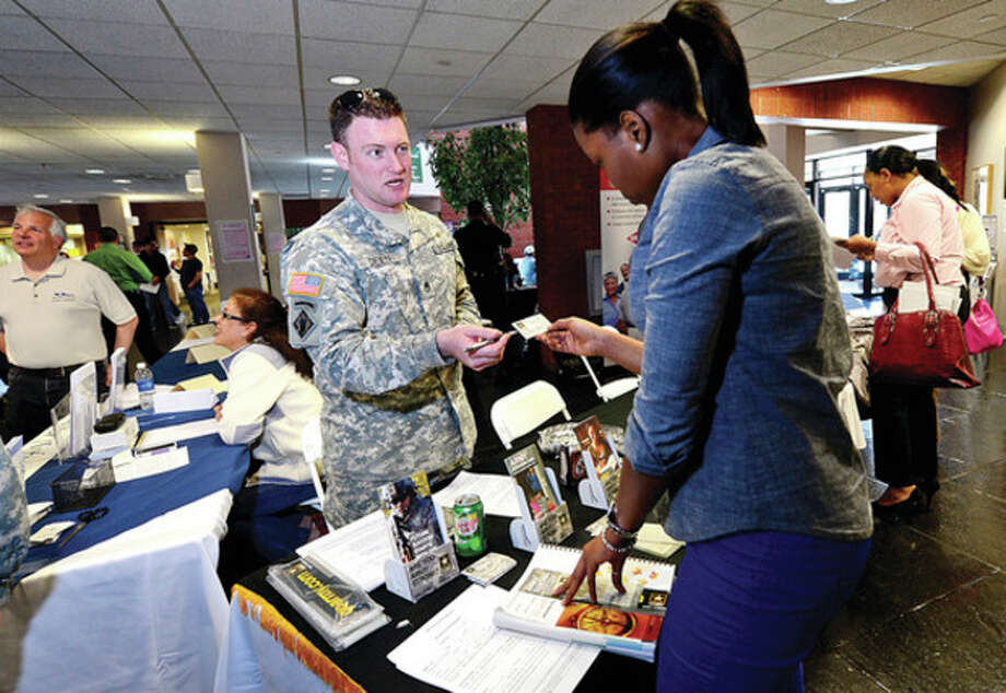 US Army Staff Seargent Timothy Deien chats with NCC student Vanessa Exantus during the Norwalk Community College Career/Job Expo 2013 in the East Campus atrium.The annual expo is a networking and information exchange event for employers to share their staffing requirements with NCC students, alumni, and community members.Hour photo / Erik Trautmann / (C)2013, The Hour Newspapers, all rights reserved