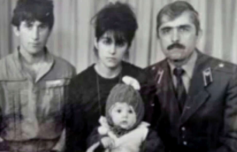 In this image taken from a video, an undated family photo provided by Patimat Suleimanova, the aunt of USA Boston bomb suspects, shows Anzor Tsarnaev left, Zubeidat Tsarnaev holding Tamerlan Tsarnaev and Anzor's brother Mukhammad Tsarnaev. Now known as the angry and grieving mother of the Boston Marathon bombing suspects, Zubeidat Tsarnaev is drawing increased attention after federal officials say Russian authorities intercepted her phone calls, including one in which she vaguely discussed jihad with her elder son. In another, she was recorded talking to someone in southern Russia who is under FBI investigation in an unrelated case, U.S. officials said. (AP Photo/Patimat Suleimanova) / Patimat Suleimanova