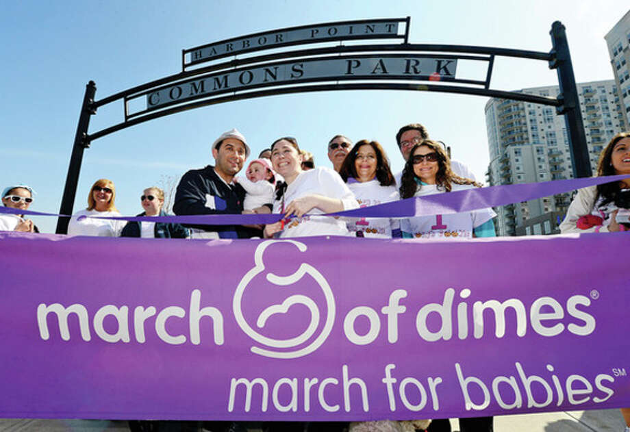 The Sklar family, including from left, Keith, Zoey, 17 months, and Michelle, who were the Ambassador family for the March of Dimes March for Babies fundraiser, cut the ribbon to start the walk Sunday at Commons Park at Harbor Point. Funds raised by March for Babies help support prenatal wellness programs, research grants, neonatal intensive care unit family support programs and advocacy efforts for stronger, healthier babies. / (C)2013, The Hour Newspapers, all rights reserved