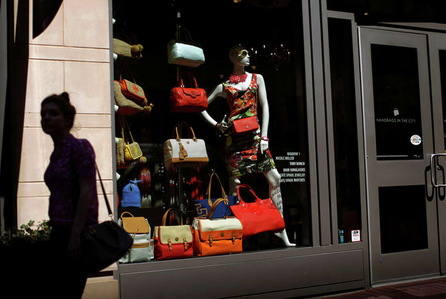 In this April 10, 2013 photo, a woman walks past a retail store's window display in Baltimore. Despite less pay, US consumers keep spending, thanks to cheaper gas, rising stocks, low rates. On Friday, April 26, 2013, the government said consumers spent 3.2 percent more on an annual basis in the January-March quarter than in the previous quarter, the biggest jump in two years. (AP Photo/Patrick Semansky) / AP