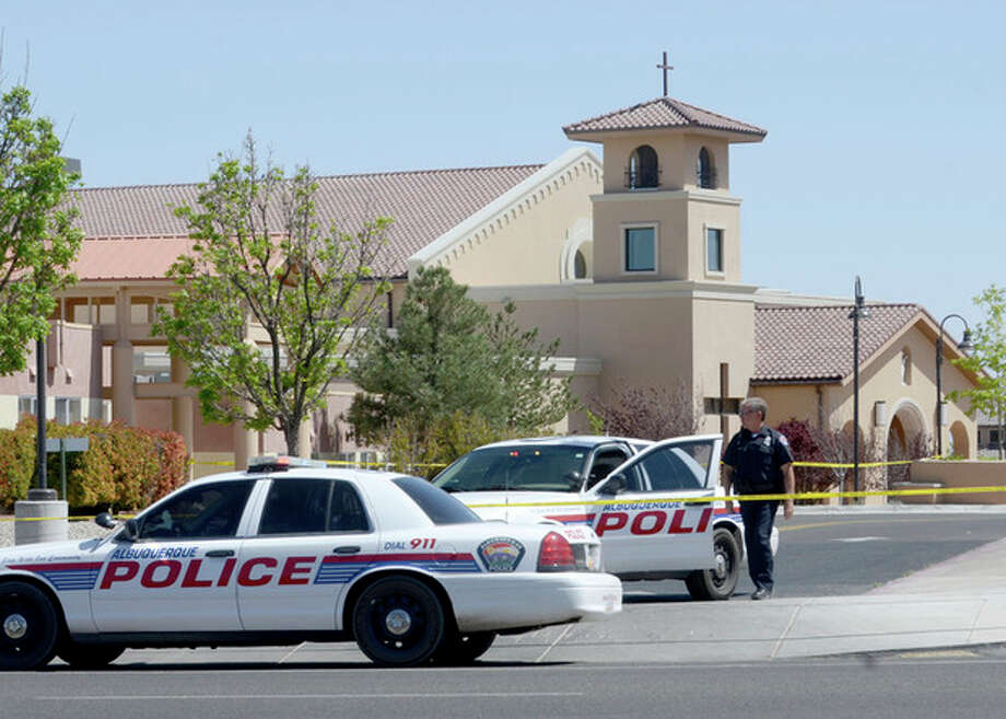 An Albuquerque Police officer walks behind the tape at St. Jude Thaddeus Catholic Church, Sunday April 28, 2013, in Albuquerque, N.M., the scene of a multiple stabbing at the conclusion of morning services. Police say a 24-year-old man stabbed four people at a Catholic church in Albuquerque as a Sunday mass was nearing its end. Police spokesman Robert Gibbs says Lawrence Capener jumped over several pews at church around noon Sunday and walked up to the choir area where he began his attack. (AP Photo/Albuquerque Journal, Dean Hanson) / The Albuquerque Journal
