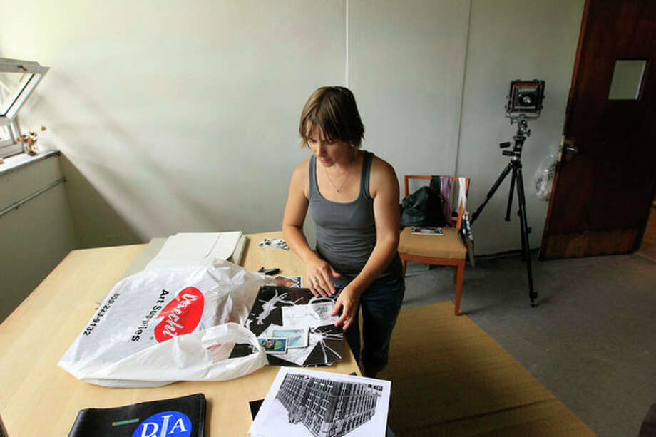 In a photo from July 24, 2012, photographer Elizabeth Sutton, 42, sorts through some materials at 555 Nonprofit Gallery and Studio, housed in a former police station in Detroit. Sutton, who is on the studio's board and an educator at the Detroit Institute of Arts, is converting space formerly used as detectives' offices into a darkroom. (AP Photo/Carlos Osorio) / AP