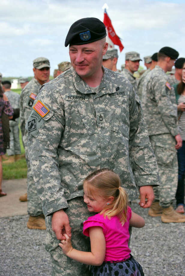 Sgt. First Class Greg Robinson, 34, of 101st Airborne Division, stands with his 4-year-old daughter, Drew, on Monday, April 29, 2013, at Fort Campbell, Ky., after graduating from air assault school. He lost a lower portion of his right leg in Afghanistan in 2006 and is the first amputee to graduate from the grueling Sabalauski Air Assault School. (AP Photo/Kristin M. Hall)