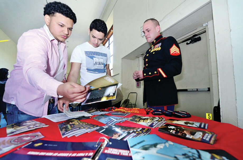Hour photo / Erik TrautmannRichard Tanales and Jean-Claude Villa get literature from Marine Corps and marine seargent Michael Torrwes during the Briggs High School Career Fair Thursday morning. / (C)2013, The Hour Newspapers, all rights reserved