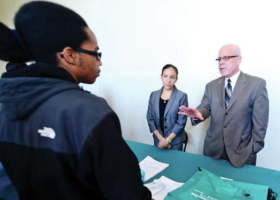 Senior Jakeem Dudely listens to a presentation from First County Bank branch manager Aitza Cabrera and VP and Regional Manager Michael Victor during the Briggs High School Career Fair Thursday morning.Hour photo / Erik Trautmann / (C)2013, The Hour Newspapers, all rights reserved