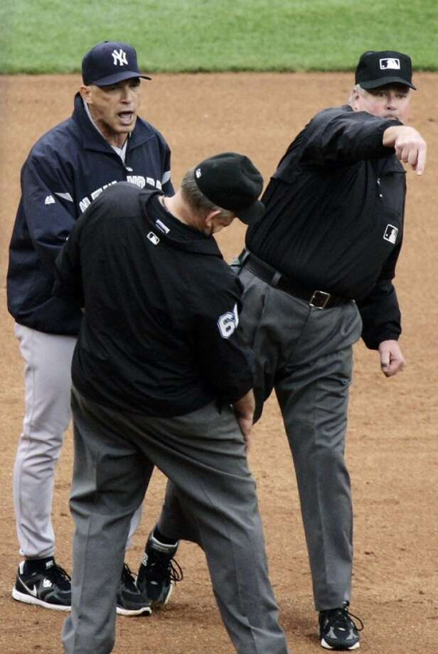 New York Yankees manager Joe Girardi, left, is tossed by third base umpire Tim Welke, right, after arguing about a double by Detroit Tigers' Andy Dirks that hit down the left field line in the fifth inning of a baseball game, Thursday, Aug. 9, 2012, in Detroit. Welke first signaled a foul ball and then signaled a fair ball on the play. Second base umpire Bob Davidson, front, looks on. (AP Photo/Duane Burleson)