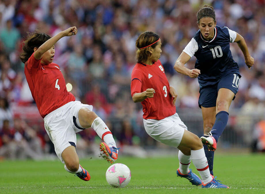United States' Carli Lloyd (10) shoots past Japan's Saki Kumagai (4) and Azusa Iwashimizu (3) during the women's soccer gold medal match at the 2012 Summer Olympics, Thursday, Aug. 9, 2012, in London. (AP Photo/Ben Curtis) / AP