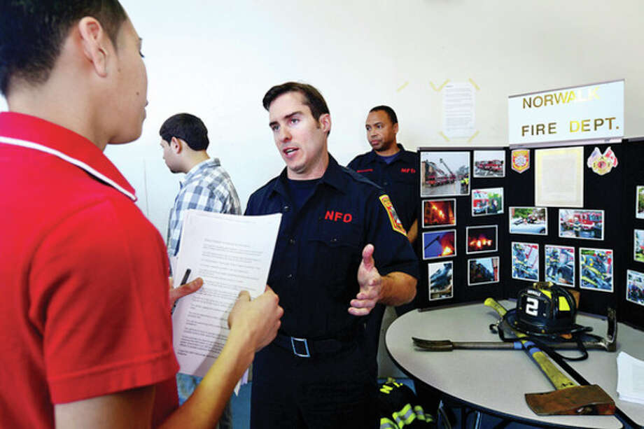 Senior Alex Ortega listens to a presentation by firefighter Brian Kaley during the Briggs High School Career Fair Thursday morning.Hour photo / Erik Trautmann / (C)2013, The Hour Newspapers, all rights reserved