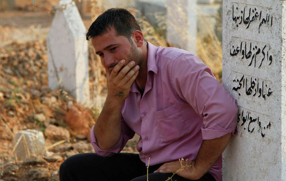 A Syrian man reacts after the funeral of 29 year-old Free Syrian Army fighter, Husain Al-Ali, who was killed during clashes in Aleppo, in the cemetery in the town of Marea on the outskirts of Aleppo city, Syria, Thursday, Aug. 9, 2012. (AP Photo/ Khalil Hamra) / AP