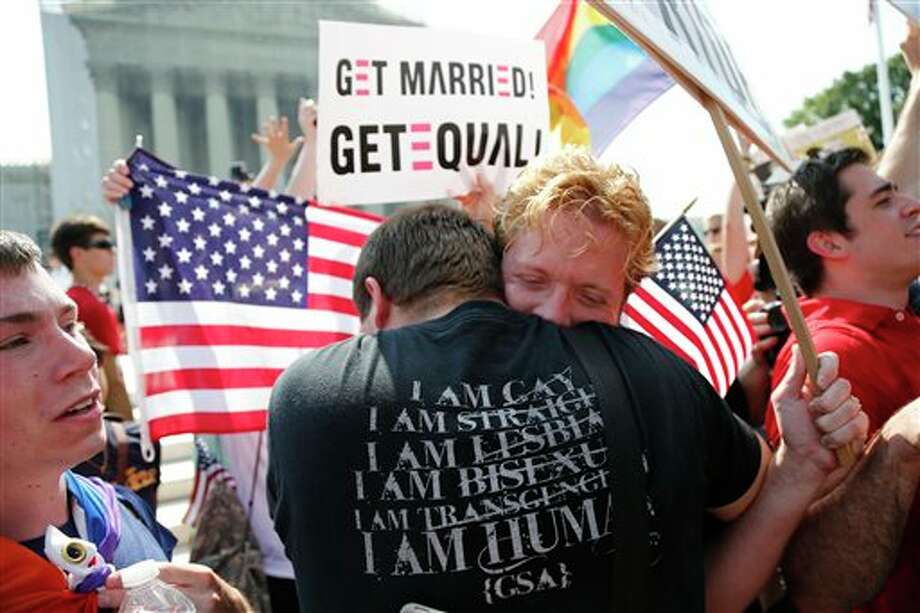 Michael Knaapen, left, and his husband John Becker, right, embrace after the Supreme Court struck down a federal provision denying benefits to legally married gay couples in front of the Supreme Court in Washington, Wednesday, June 26, 2013. In a major victory for gay rights, the Supreme Court on Wednesday struck down a provision of a federal law denying federal benefits to married gay couples and cleared the way for the resumption of same-sex marriage in California. (AP Photo/Charles Dharapak) / AP