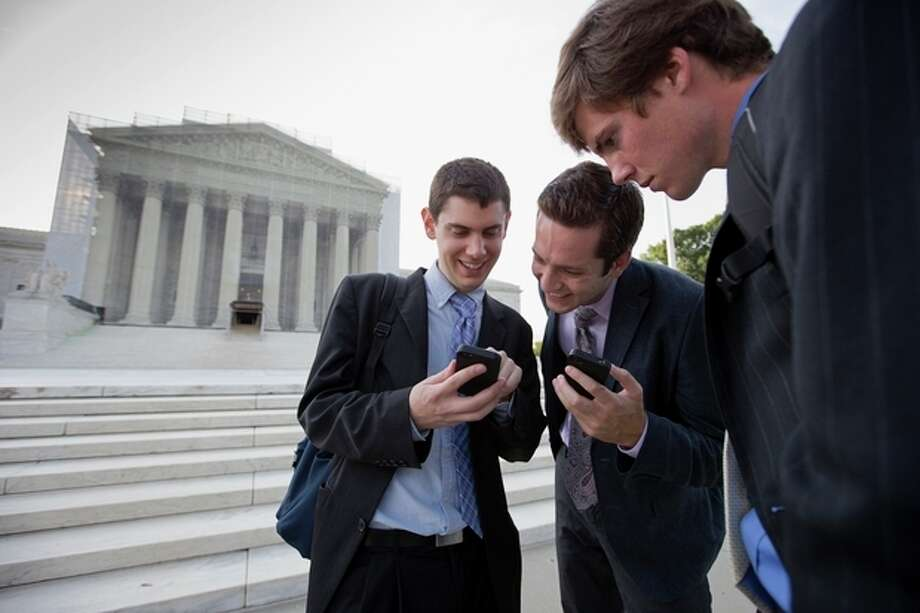 After delivering coffee to visitors to waiting to enter the Supreme Court, SCOTUS Blog interns check their smartphones for updates on the latest news as outside the court in Washington, Wednesday, June 26, 2013, as the justices are expected to hand down major rulings on two gay marriage cases that could impact same-sex couples across the country. From left to right are Dan Stein, Max Mallory, and Andrew Hamm. (AP Photo/J. Scott Applewhite) / AP