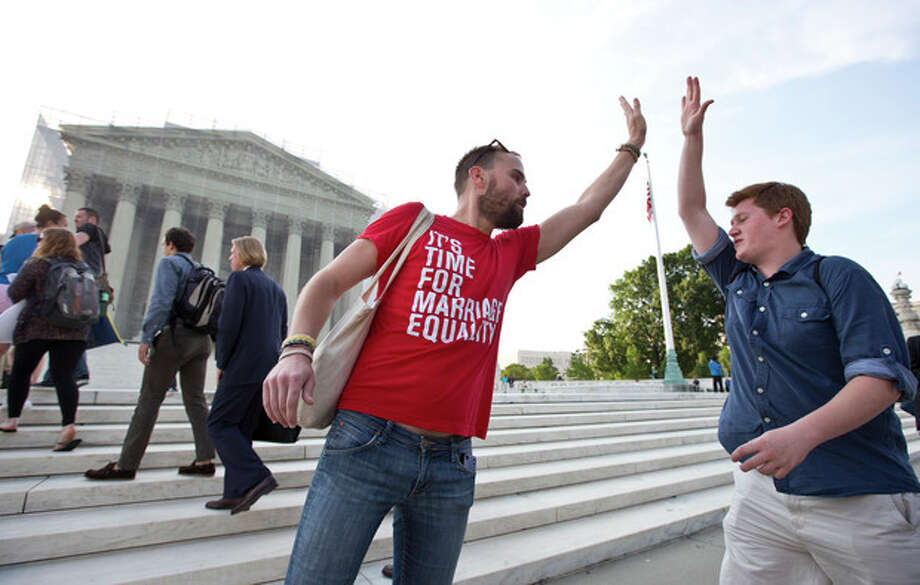 Gay rights activist Bryce Romero, who works for the Human Rights Campaign, offers an enthusiastic high-five to visitors getting in line to enter the Supreme Court on a day when justices are expected to hand down major rulings on two gay marriage cases that could impact same-sex couples across the country, in Washington, Wednesday, June 26, 2013. (AP Photo/J. Scott Applewhite) / AP