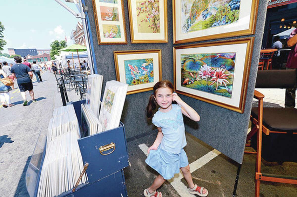 Jenna Kornbluth, 6, enjoys looking at art during The 37th Annual SoNo Arts celebration Saturday. Hour photo / Erik Trautmann